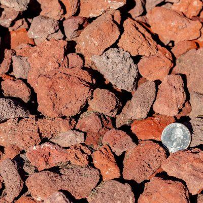 1-1/2 inch Black Lava Stones with Quarter Comparison