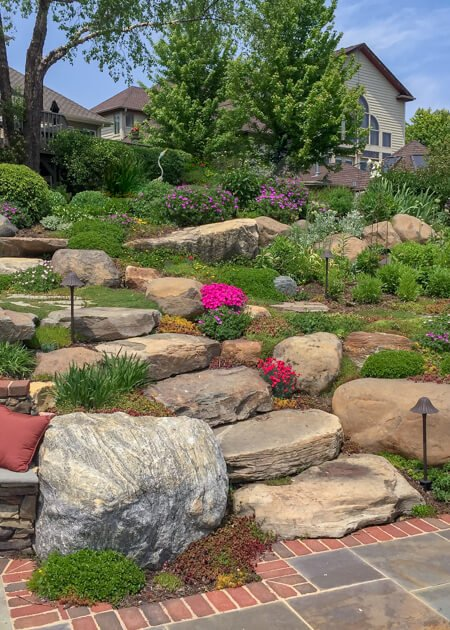 Landscape work with bushes, lights, decorative stones, and colorful plants